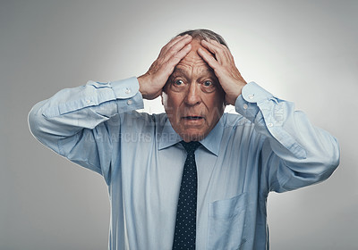 Buy stock photo Shot of a senior businessman standing against a grey studio background with his head in his hands and looking stressed