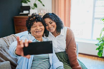 Buy stock photo Shot of a young man taking selfies with his elderly relative on the sofa at home