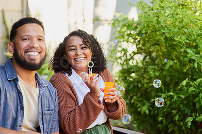 Buy stock photo Shot of a young man and woman blowing bubbles in a garden