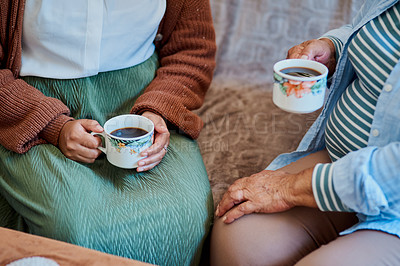 Buy stock photo Shot of an unrecognisable young woman having coffee with her elderly relative on the sofa at home