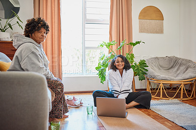 Buy stock photo Shot of an elderly woman working out the sofa while her daughter uses a laptop at home