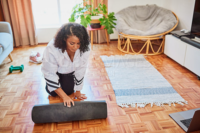 Buy stock photo Shot of a young woman rolling out her exercise mat in preparation for a yoga routine at home
