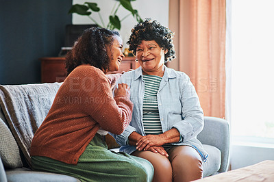 Buy stock photo Shot of an elderly woman relaxing with her daughter on the sofa at home