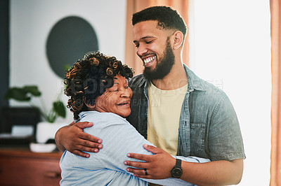 Buy stock photo Shot of a young man bonding with his elderly relative at home