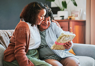 Buy stock photo Shot of a young woman giving her elderly relative a present on the sofa at home