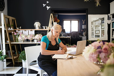 Buy stock photo Cropped shot of an attractive young woman writing in a notebook while working in her flower shop