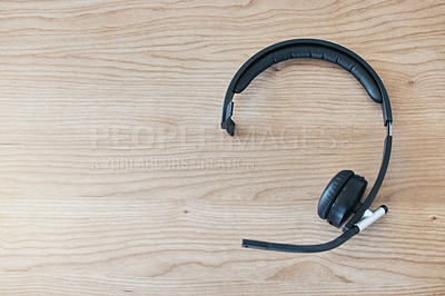 Buy stock photo Shot of a set of headsets lying on a desk in an empty office during the day