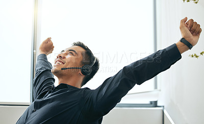 Buy stock photo Shot of a handsome young salesman sitting alone in his office and feeling successful while wearing a headset