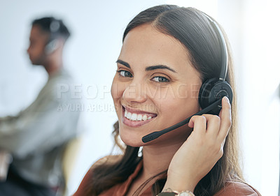 Buy stock photo Shot of an attractive young saleswoman sitting with a colleague in the office and wearing a headset
