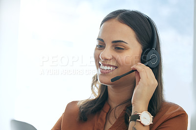 Buy stock photo Shot of an attractive young saleswoman sitting alone in her office and wearing a headset