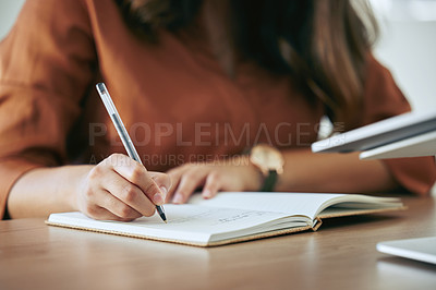 Buy stock photo Cropped shot of an unrecognizable businesswoman sitting alone in her office and writing in a notebook