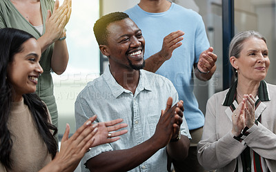 Buy stock photo Shot of a young businessman applauding with his colleagues in an office