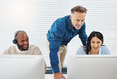 Buy stock photo Shot of two call centre agents sitting in the office and using their computers while getting help from their manager