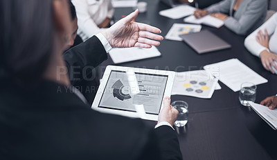 Buy stock photo Shot of a mature businesswoman using a digital tablet during a business meeting