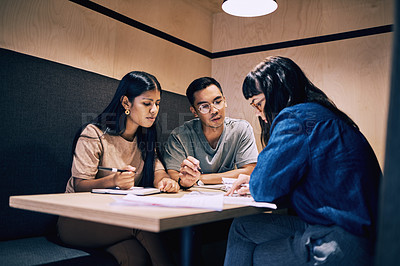 Buy stock photo Shot of a group of businesspeople going over paperwork together