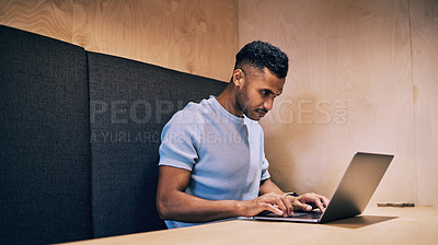 Buy stock photo Shot of a young businessman using his laptop to complete his work