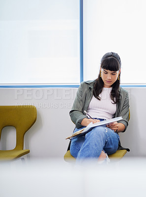 Buy stock photo Shot of a young woman filling in an application for a job at a modern office