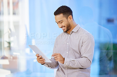 Buy stock photo Shot of a businessman using a digital tablet while standing in a modern office