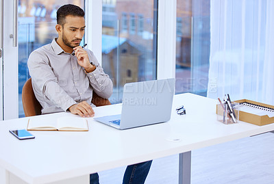 Buy stock photo Shot of a businessman looking at his laptop while sitting at his desk