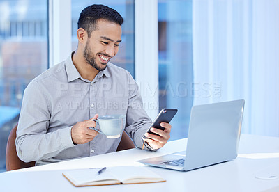 Buy stock photo Shot of a young businessman using his cellphone and drinking coffee while sitting at his desk