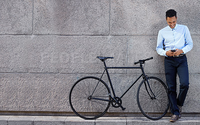 Buy stock photo Full body shot of young businessman standing next to a bicycle while using a cellphone against a grey urban wall