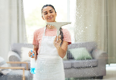 Buy stock photo Shot of a young woman cleaning the windows at home