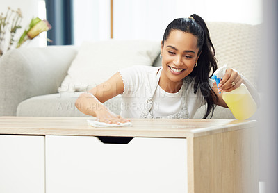 Buy stock photo Shot of a young woman looking happy while doing chores at home