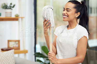 Buy stock photo Shot of a happy young woman holding a mop in her living room at home