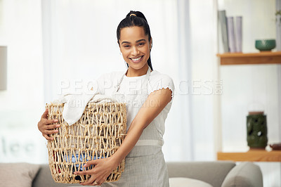 Buy stock photo Shot of a happy young woman holding a laundry basket at home