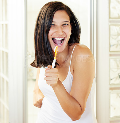 Buy stock photo Shot of a beautiful young woman brushing her teeth at home