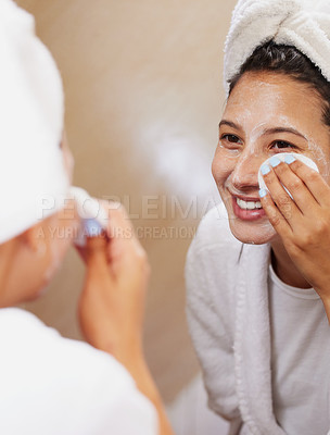 Buy stock photo Shot of a beautiful young woman looking in the mirror while cleaning her face