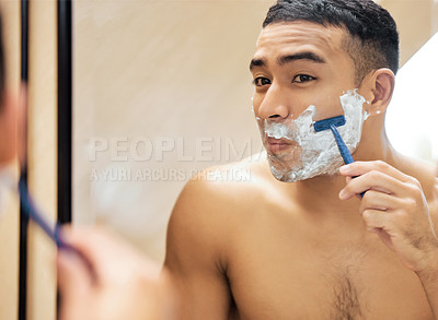 Buy stock photo Shot of a young man looking in the mirror while shaving his beard