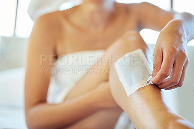 Buy stock photo Cropped shot of an unrecognizable woman waxing her legs at home