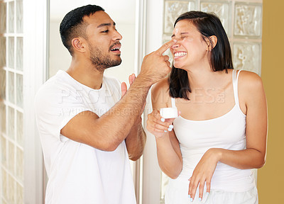 Buy stock photo Shot of a playful couple going through their morning routine at home