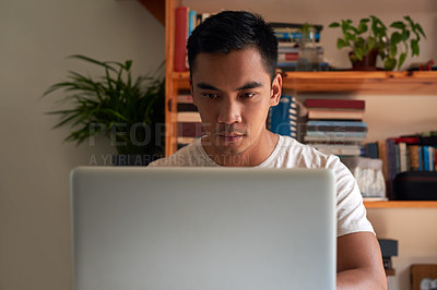 Buy stock photo Shot of a handsome young man sitting alone in his home office and using his laptop to work