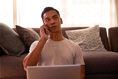 Buy stock photo Shot of a handsome young man sitting alone in his living room and using his laptop and cellphone to work