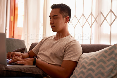 Buy stock photo Shot of a handsome young man sitting alone in his living room and using his laptop to work from home