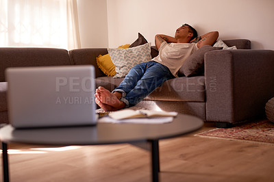 Buy stock photo Shot of a handsome young man lying on the sofa in his living room and sleeping