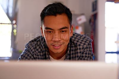 Buy stock photo Shot of a handsome young man sitting alone at his kitchen counter and using his laptop to work from home