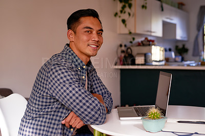 Buy stock photo Shot of a handsome young man sitting alone and using his laptop to work from home