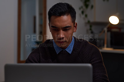 Buy stock photo Shot of a young businessman working late on a laptop at home