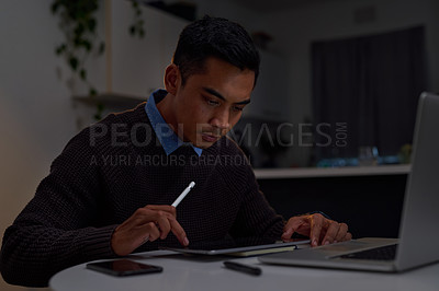 Buy stock photo Shot of a young businessman using a tablet while working late at home