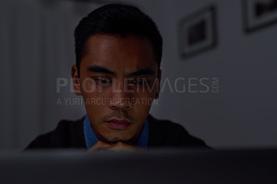 Buy stock photo Shot of a young businessman looking at a laptop while working late at home