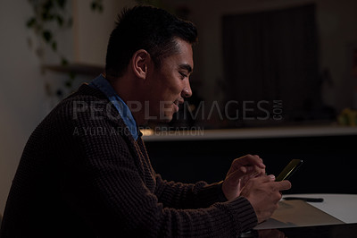 Buy stock photo Shot of young businessman using his cellphone while working late at home