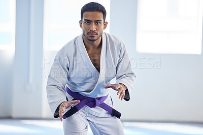 Buy stock photo Cropped portrait of a handsome young male martial artist standing in fight stance in the gym