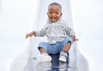 Buy stock photo Shot of a baby boy playing on the slide  in the park