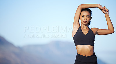 Buy stock photo Portrait of a sporty young woman stretching her arms while exercising outdoors