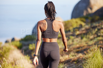 Buy stock photo Rearview shot of a sporty young woman walking along a path outdoors