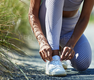 Buy stock photo Closeup shot of an unrecognisable woman tying her shoelaces while exercising outdoors