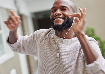 Buy stock photo Shot of a young man dancing while listening to music at home